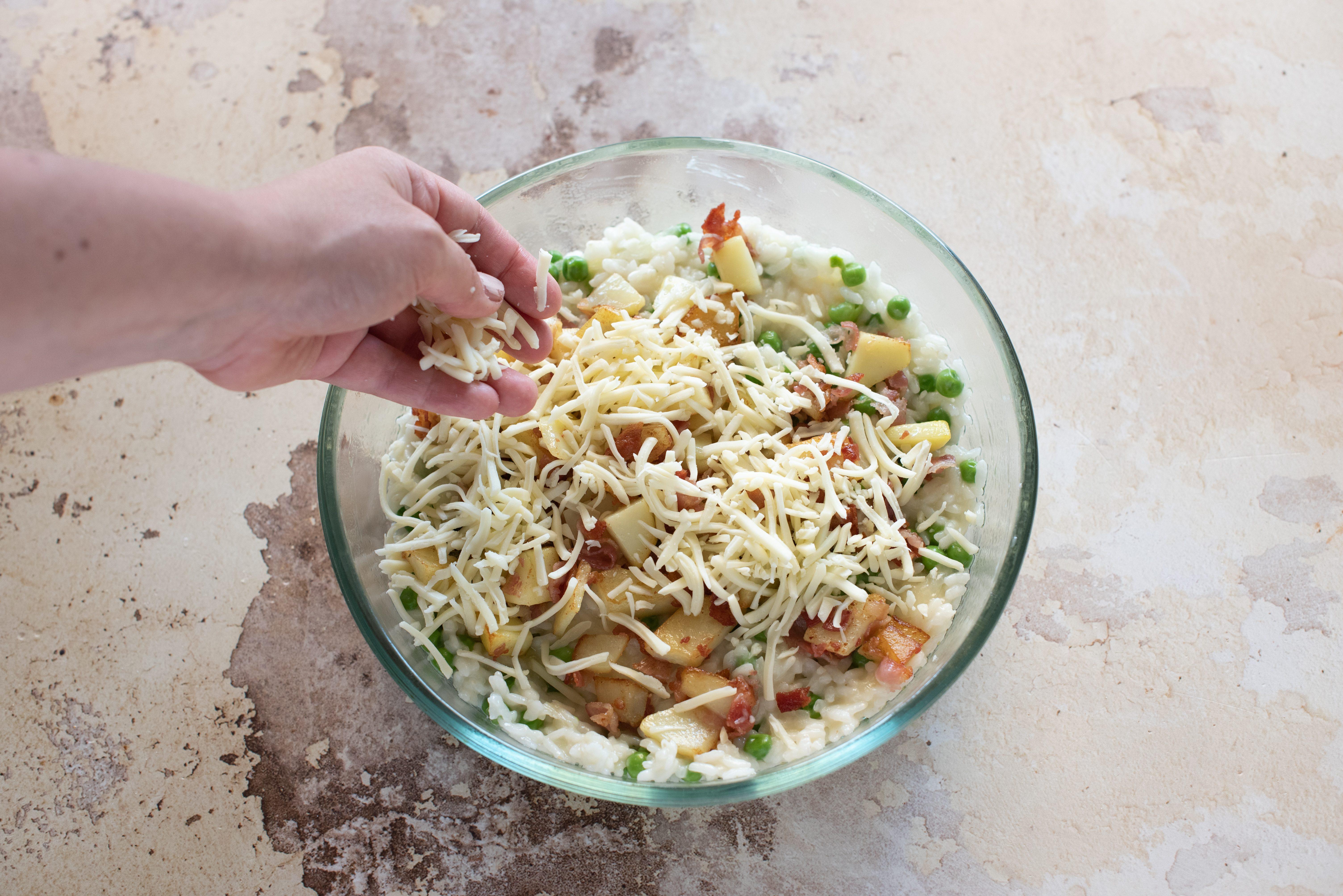 Riso al forno con piselli, pancetta e patate, aggiungere provola